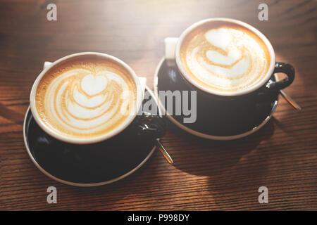 Zwei Tassen Cappuccino und Latte Kunst auf Holztisch. Close Up. Stockfoto