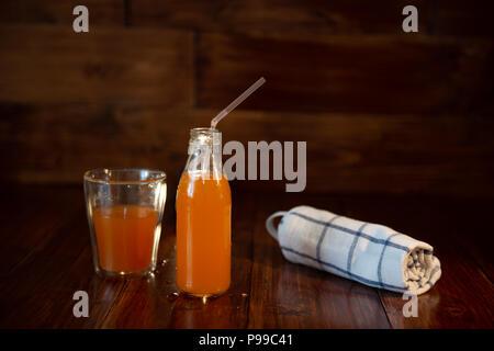 Vintage Flasche mit Saft, Stroh und Handtuch auf hölzernen Tisch - Stockfoto