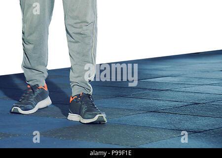 Die Beine Junge Mode Mann und Schuhe auf dem Holzboden, Mann an der Turnhalle Posing ist - Stockfoto