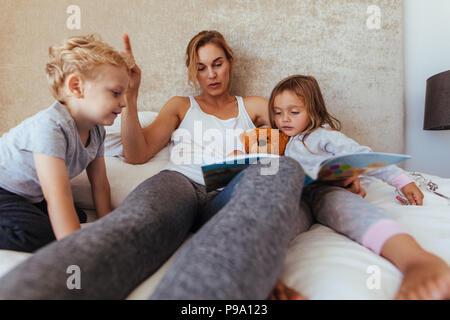 Mutter Lesung Gute-Nacht-Geschichte für Kinder zu Hause. Fürsorgliche Mutter lesen Buch für entzückende kleine Kinder auf dem Bett. - Stockfoto