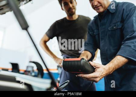Kfz-mechaniker Holding ein Gerät zur Prüfung der Bedingung. Mechanik Diagnose eines Auto Motor mit Gerät in Service Station. - Stockfoto