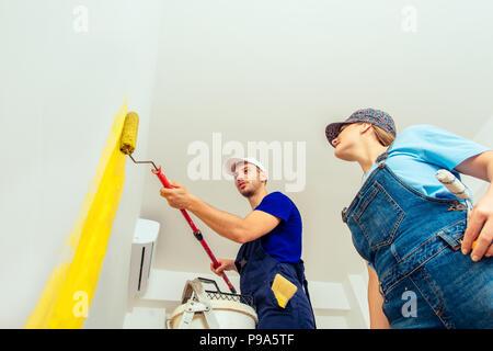 ... Paar Trägt Blaue Overalls Malerei Ihre Wohnzimmer In Der Farbe Gelb    Stockfoto