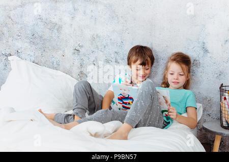 Schöne Mädchen ist das Lesen eines Buches zu ihrem Bruder im Bett Stockfoto