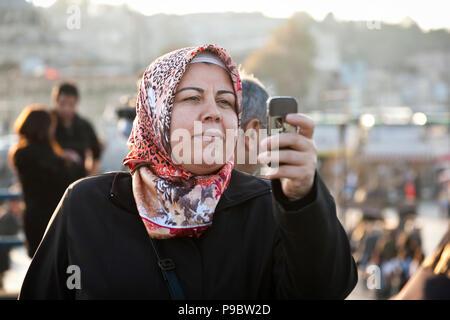Istanbul, Türkei - 6 November 2009: Frau mit Kopftuch mit Ihrem Mobiltelefon ein Foto während der Galata Brücke in Istanbul zu nehmen - Stockfoto