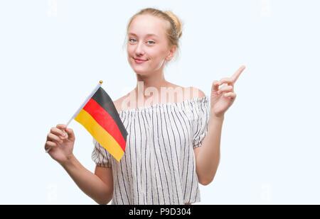 Blonde Teenager Frau mit Flagge Deutschlands sehr zufrieden zeigt mit Finger- und an der Seite - Stockfoto