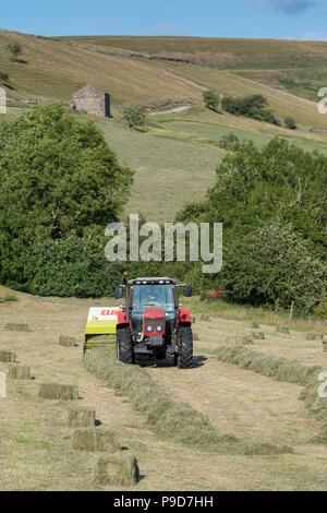 Landwirt in Swaledale, North Yorkshire, Heuballen, mit einem Massey Ferguson 5470 und ein CLAAS Rundballenpresse. - Stockfoto
