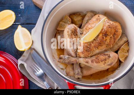 Das ganze Huhn gebacken mit Zitrone und Rosmarin in einer roten Gusseisen. Blau Holz- Hintergrund und grau Handtuch. Messer und Gabel. Freier Platz für Text. - Stockfoto