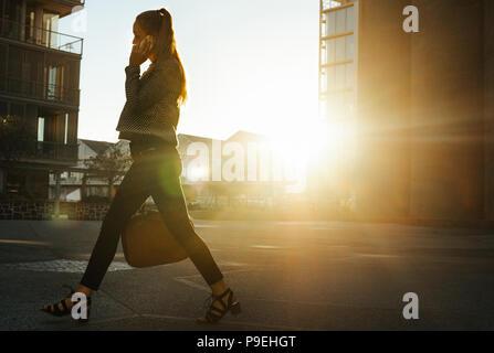 Geschäftsfrau Pendeln zum Amt früh am Morgen sprechen über Handy. Frau, die Handtasche zu Fuß auf der Straße zu. - Stockfoto