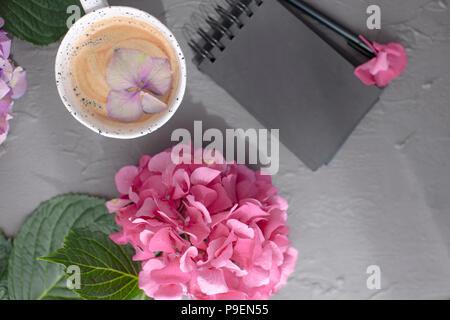 Eine Tasse duftenden Kaffee und rosa Hortensie Blumen, auf einem grauen Hintergrund, freier Platz für Text und einem schwarzen Notepad. Karte, Kopieren Raum - Stockfoto