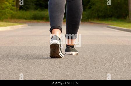 Eine junge Frau in Turnschuhen und Jeans entlang eine Asphaltstraße in der Nähe von einem Wald bei einem sommerlichen Abend - Stockfoto