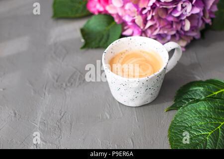 Eine Tasse duftenden Kaffee und rosa Hortensie Blumen, auf einem grauen Hintergrund, freier Platz für Text. Karte, Kopieren Raum - Stockfoto