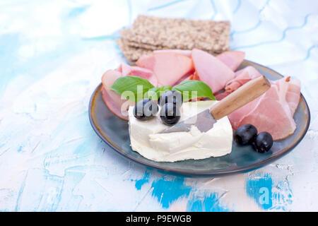 Käse und Schinken mit Oliven auf einem grauen Platte. Weißer Hintergrund mit blauen Scheidungen. Messer für Käse. Trockene Breadstones. Freier Platz für Text oder eine Postkarte. - Stockfoto