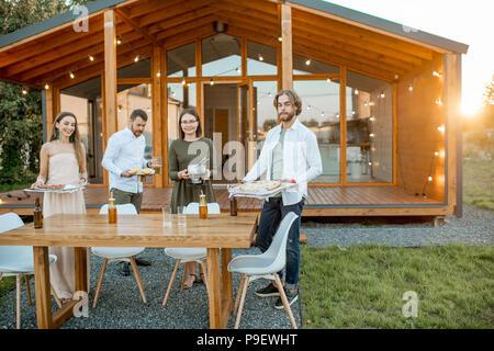 Freunde die Vorbereitung für das Abendessen in der Nähe des Hauses - Stockfoto