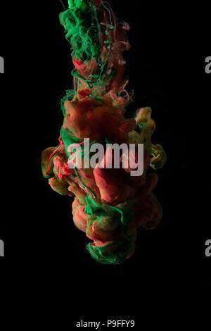 Grüne und rote Tinte fließt in Wasser und zusammen mischen auf schwarzem Hintergrund. - Stockfoto
