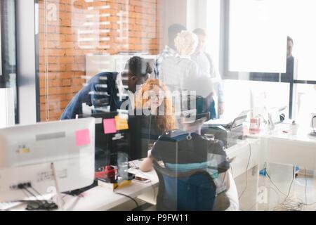 Zwei afrikanische Büromitarbeiter vorzuleuchten dabei helfen, ihre Rothaarige Partner in den belebten Raum mit Glaswänden - Stockfoto