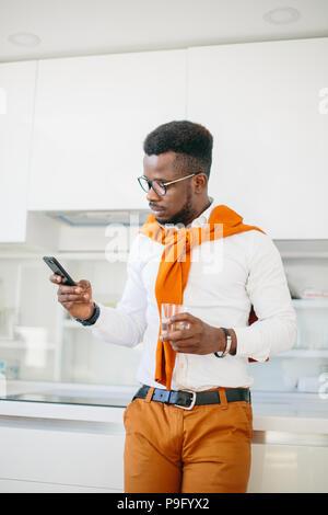 Nahaufnahme Seitenansicht schoss der Mode Africanamerican Kerl ein Glas Wasser halten und einen Anruf im Speisesaal mit moderner Inneneinrichtung. - Stockfoto