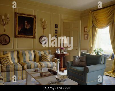 ... Gelb Und Blau Gestreiften Sofa Und Blauen Sessel In Creme Getäfelten  Wohnzimmer Mit Swagged Gelbe Vorhänge