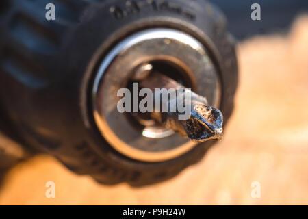 Schraube, die in ein Stück Holz von Akkuschrauber verschraubt. Konzept Werkzeuge und Reparaturarbeiten. - Stockfoto