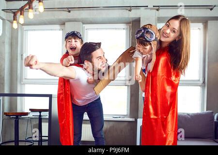 Happy Family im Superhelden Kostüme spielen. - Stockfoto