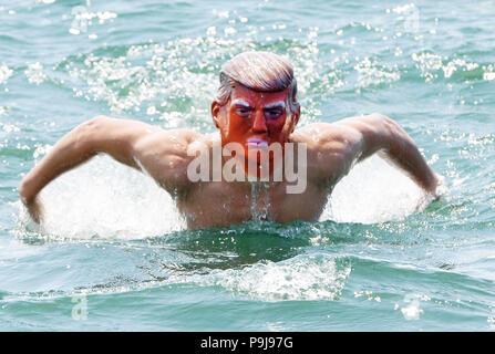 Mann in Donald Trump Maske genießen die Sonne in Plymouth, Devon, Großbritannien - Stockfoto