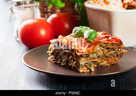 Stück leckeren heißen Lasagne mit Spinat auf einen Teller. Italienische Küche. - Stockfoto