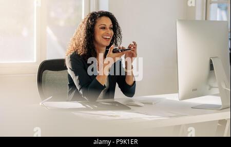 Lächelnde Frau Unternehmer an Ihrem Schreibtisch im Büro sprechen über Mobiltelefon auf Lautsprecher. Frau sitzen vor dem Computer im Büro sprechen auf Zelle Ph - Stockfoto