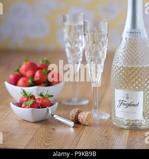 Prosecco und Erdbeeren geschliffene Gläser Blume wallpaper hölzernen Tischplatte weißes Porzellan Geschirr - Stockfoto