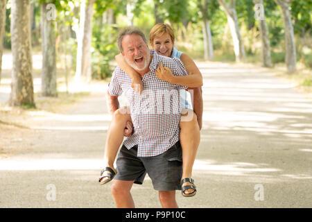 Glücklich lächelnde senior Paar in Liebe, Entspannung, Tanz und Spaß in den Park. Gemeinsam stark, Ruhestand, glückliches Leben Konzept. - Stockfoto