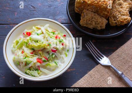 Salat aus frischen Kohl, Radieschen, Gurken, Paprika und saure Sahne in eine weiße Platte, Maisbrot und schwarzen Stecker auf alten Desktop. Top vie - Stockfoto