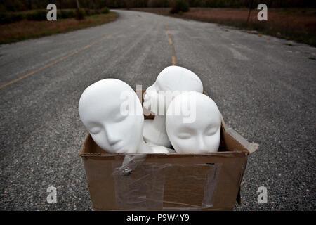 Styropor Mannequin heads sitzen in einem Karton in einem verlassenen Parkplatz - Stockfoto
