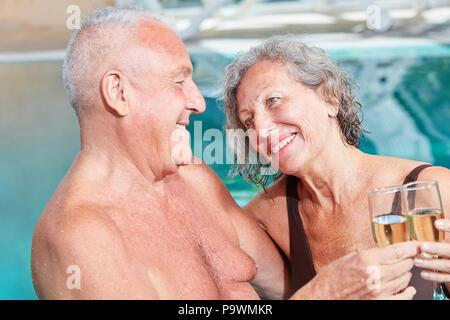 Senior Paar feiert mit Sekt im Swimmingpool, der während einem Wellness Urlaub - Stockfoto