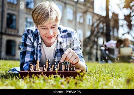 Hübscher junger Mann spielt Schach im Freien