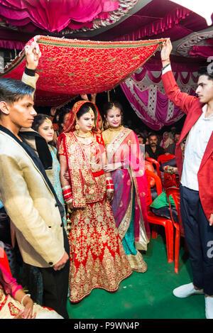 Eine traditionelle Hochzeit in einem kleinen Dorf in der indischen Provinz. Indie Juni 2018. Die Trauzeugen bringen die Braut zum Bräutigam.