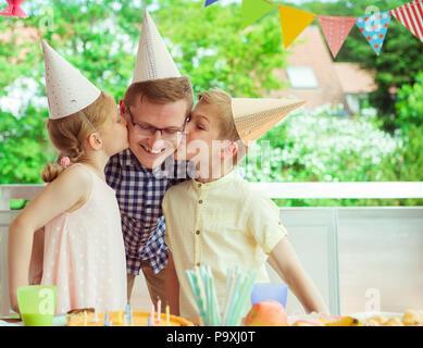 Zwei süße Kinder küssen ihre junge und glückliche Vater bei seiner Geburtstagsfeier auf bunt dekorierten Terrasse zu Hause - Stockfoto