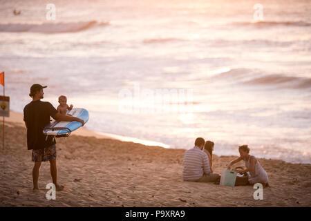 Mit Baby auf Surfboard und andere Surfer am Strand bei Sonnenuntergang, Oahu, Hawaii Inseln, USA - Stockfoto