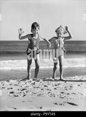 1930er Jahre ZWEI KINDER jungen Mädchen halten sich an den Händen, die auf sandigen Strand - BX 001393 CAM001 HARS FREUNDSCHAFT IN VOLLER LÄNGE PERSONEN MÄNNER GESCHWISTER SURF SCHWESTERN B&W SOMMER AUGENKONTAKT UFER GLÜCK AUFREGUNG ERHOLUNG CAM001 halten sich an den Händen GESCHWISTER SANDY BADEANZUG BADEMODEN Wachstum von Jungfischen SEASHORE ZWEISAMKEIT SCHWARZ UND WEISS KAUKASISCHEN ETHNIE ALTMODISCH - Stockfoto