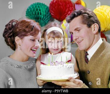 1960 lächelnde Mutter und Vater mit Tochter bereit, blasen Sie die Kerzen auf der Geburtstagstorte PARTY DEKORATIONEN - KJ 3953 HAR 001 HARS DRINNEN NOSTALGISCHE PAAR FARBE MÜTTER ALTE ZEIT NOSTALGIE OLD FASHION 1 KINDER DEKORATIONEN GERNE FAMILIEN FREUDE LIFESTYLE FEIER FRAUEN BEREIT VERHEIRATET STUDIO SHOT EHEPARTNER GESUNDHEIT LEBEN ZU HAUSE KOPIEREN PLATZ DAMEN TÖCHTER PERSONEN MÄNNER VÄTER GLÜCK KOPF UND SCHULTERN FRÖHLICH UND VATIS AUFREGUNG LÄCHELT VERBINDUNG FREUDIGE ZUSAMMENARBEIT Wachstum von Jungfischen Mitte - Mitte - erwachsenen Mann Mitte der erwachsenen Frau MAMMEN ZWEISAMKEIT FRAUEN KAUKASISCHEN ETHNIE HAR 001 ALTMODISCH - Stockfoto