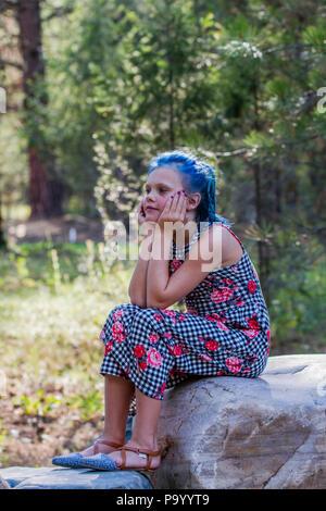 Atrtractive 8 jähriges Mädchen, in bunten jump Suit, Haare gefärbt ist hellblau, sitzen auf den Felsen, tief in Gedanken, Seite Profil. . Model Release #113 - Stockfoto