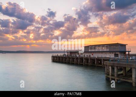Dorchester, Dorset, Großbritannien. Juli 2018 20. UK Wetter. Die aufgehende Sonne hinter Wolken am frühen Morgen an der Pleasure Pier in den Badeort Weymouth in Dorset an einem warmen abgerechnet. Foto: Graham Jagd-/Alamy leben Nachrichten - Stockfoto