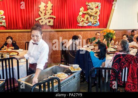 Orlando Florida Chinatown Lam's Garden Chinese Restaurant Dim Sum ethnischen Restaurants große Familie Tabelle asiatische Frau Mann Kellnerin Warenkorb server Innenraum - Stockfoto