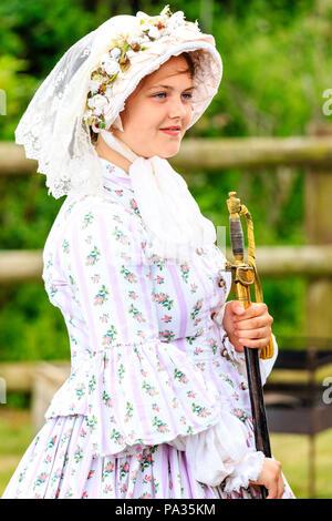 Blonde junge Teenager Mädchen, 14-15 Jahre, trug im Viktorianischen Kostüm, Hut und Kleid, und halten Schwert an Re-enactment Dickens Veranstaltungen in Broadstairs. - Stockfoto