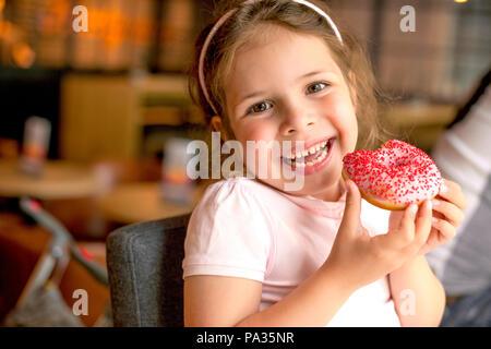 Happy girl essen Kuchen in einem Cafe. Schädliche süße Speisen. Trends in der Nahrung. Platz kopieren