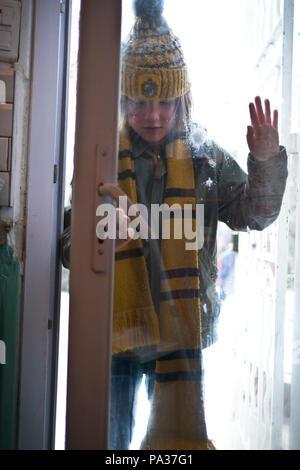 Emotionale Low Angle Shot von zehn Jahre alten Jungen in Winterkleidung in sein Haus kommen nach Schneeballschlacht gekleidet - Stockfoto