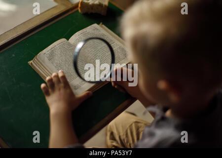 Ein Junge, der Blick aus dem Fenster in dem alten Haus, auf der Suche nach jemandem, einer geheimnisvollen Landschaft, ein Foto für die Titelseite des Buches. - Stockfoto