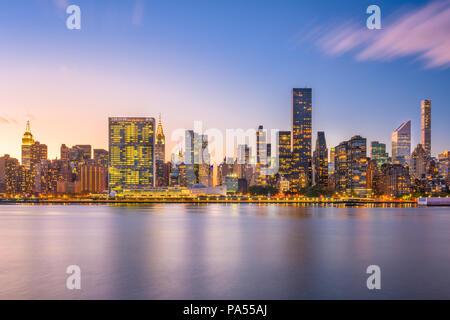 New York, New York, USA die Skyline von Midtown aus über dem East River in der Abenddämmerung. Stockfoto