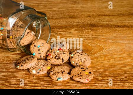 Choc Chip Cookies smartie Fallen aus Glas auf Holz- Tisch. - Stockfoto