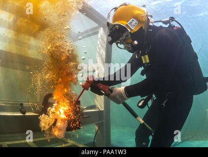 Us Navy Lieutenant Christopher Ferguson, NECC dive Medical Officer für die Unterwasser Bauteams, schneidet eine Stahlplatte mit einer exothermen Schneidbrenner in einem lehrschwimmbecken in der Republik Korea (ROK) Engineering School in Jinhae, ROK, 17. März 2016 während der Übung Fohlen Adler 2016. Fohlen Eagle ist eine jährliche, bilateralen Training konzipiert, der die Bereitschaft der USA und ROK Kräfte zu erhöhen, und ihre Fähigkeit, gemeinsam während einer Krise zu arbeiten. (U.S. Marine bekämpfen Kamera Foto von Mass Communication Specialist 1. Klasse Charles E. Weiß/Freigegeben) - Stockfoto
