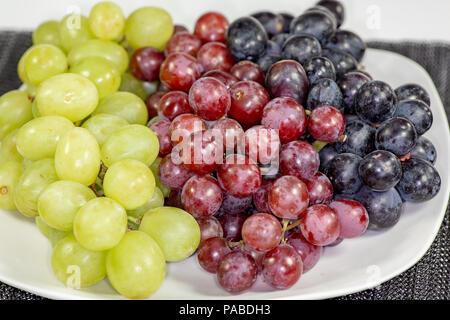 Schwarz, Rot, Grün kernlose Trauben in einer tiefen weiße Schüssel auf einem weißen Geschichte warten auf Frühstück gegessen zu werden. - Stockfoto