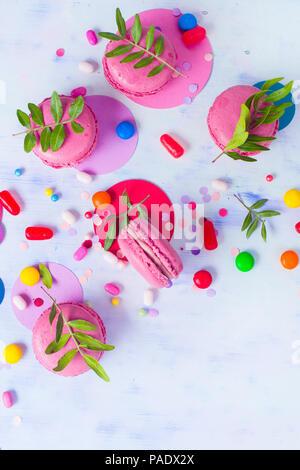 Macaroon Cookies auf einen farbigen Hintergrund mit Konfetti. Lebendige Partei Konzept mit kopieren. Rosa und Lila palette Flach. - Stockfoto