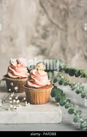 Cupcakes mit buttercream auf Marmor. Luxus Hochzeit oder Geburtstag Cupcakes. Getonten Bild - Stockfoto